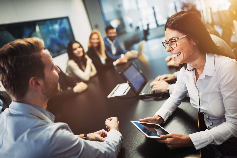 Imagem de pessoas sorrindo em uma mesa de reunião para remeter ao contador feliz