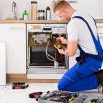 Foto de um homem arrumando um fogão depois que ele iniciou seu projeto de como montar um serviço de manutenção de eletrodomésticos