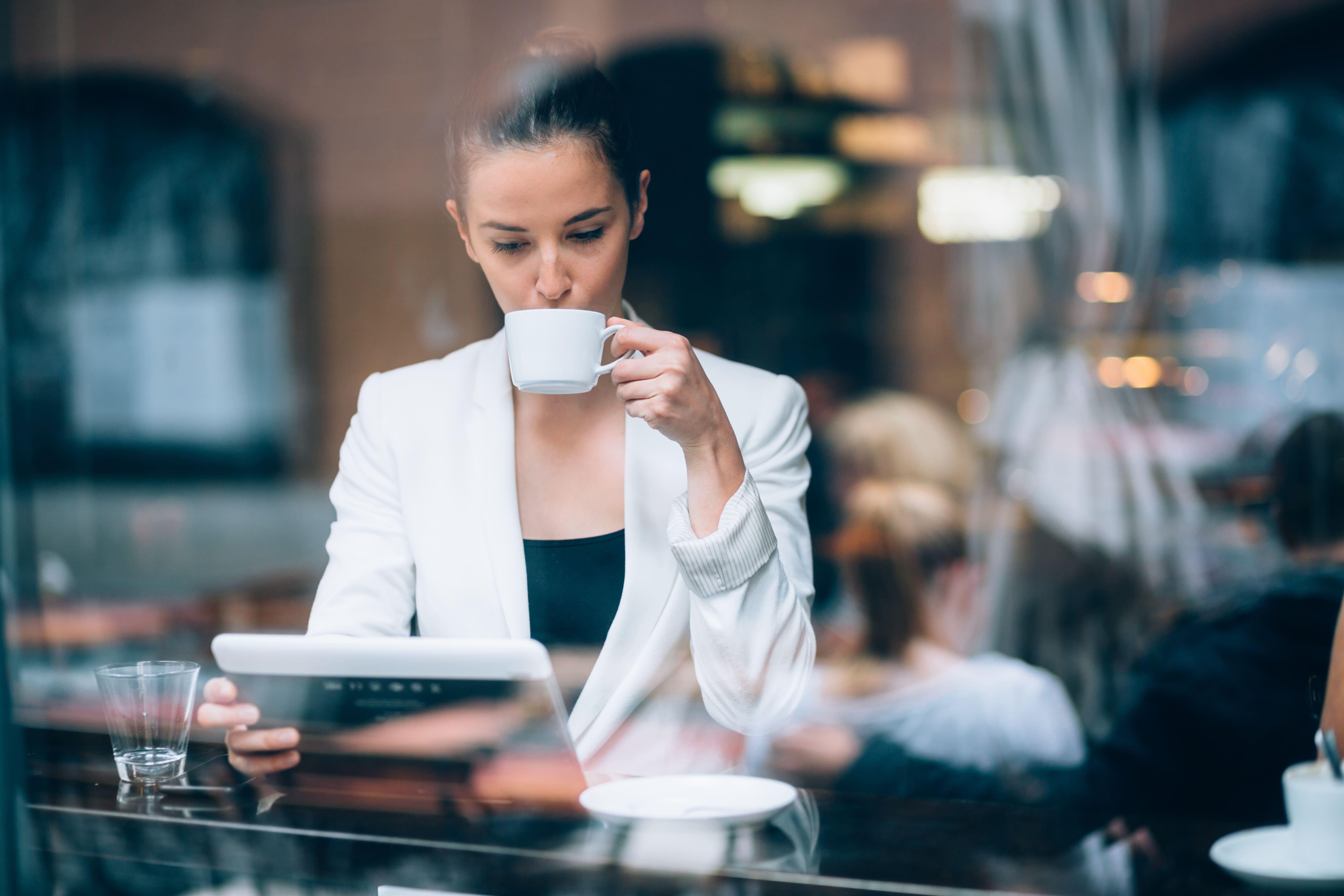 Mulher tomando um café e lendo a matéria do abertura simples de como empreender em Potim