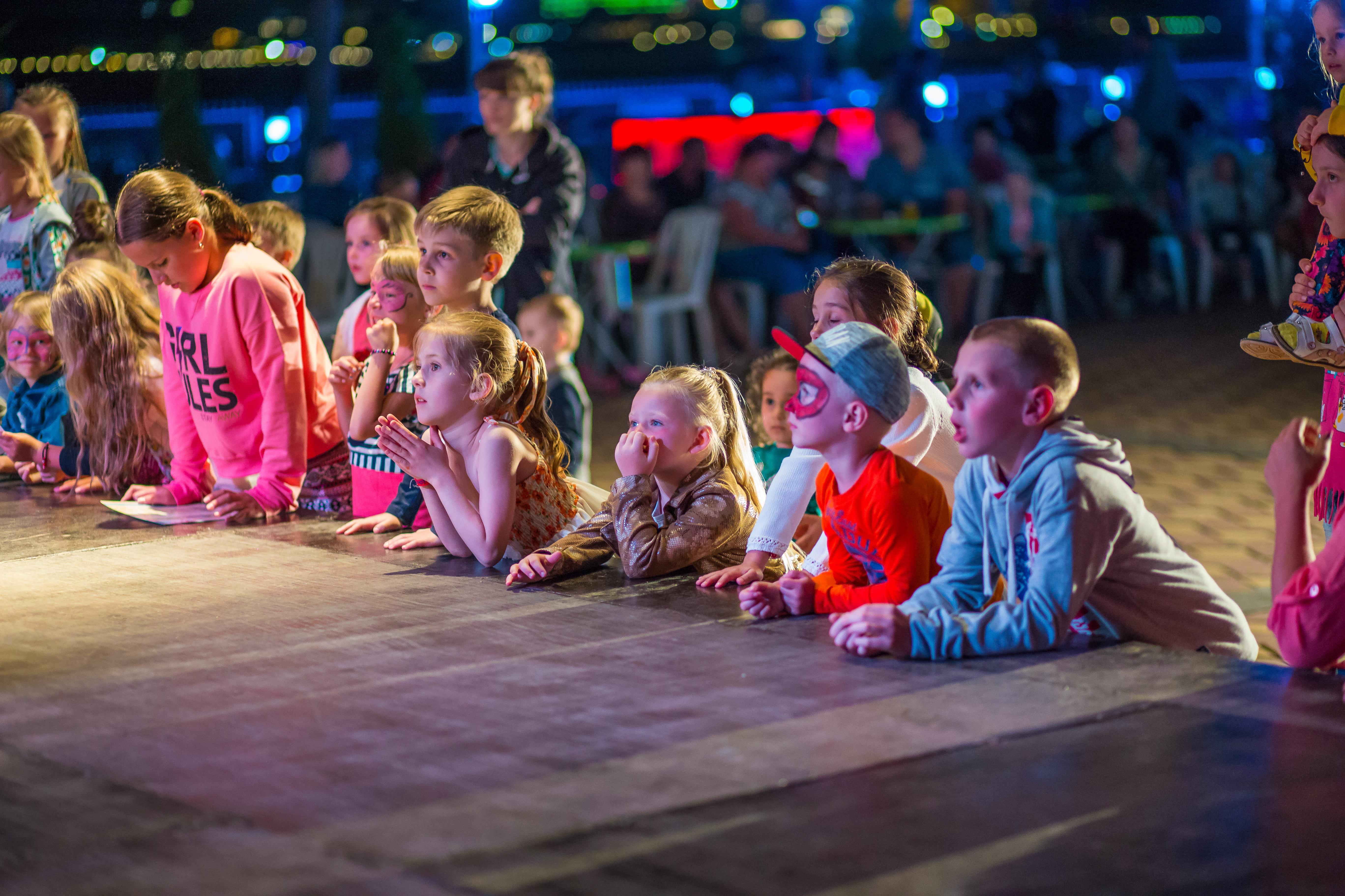 Imagem das crianças vendo uma apresentação de teatro de um empreendedor que resolveu montar um serviço de animação de festa infantil