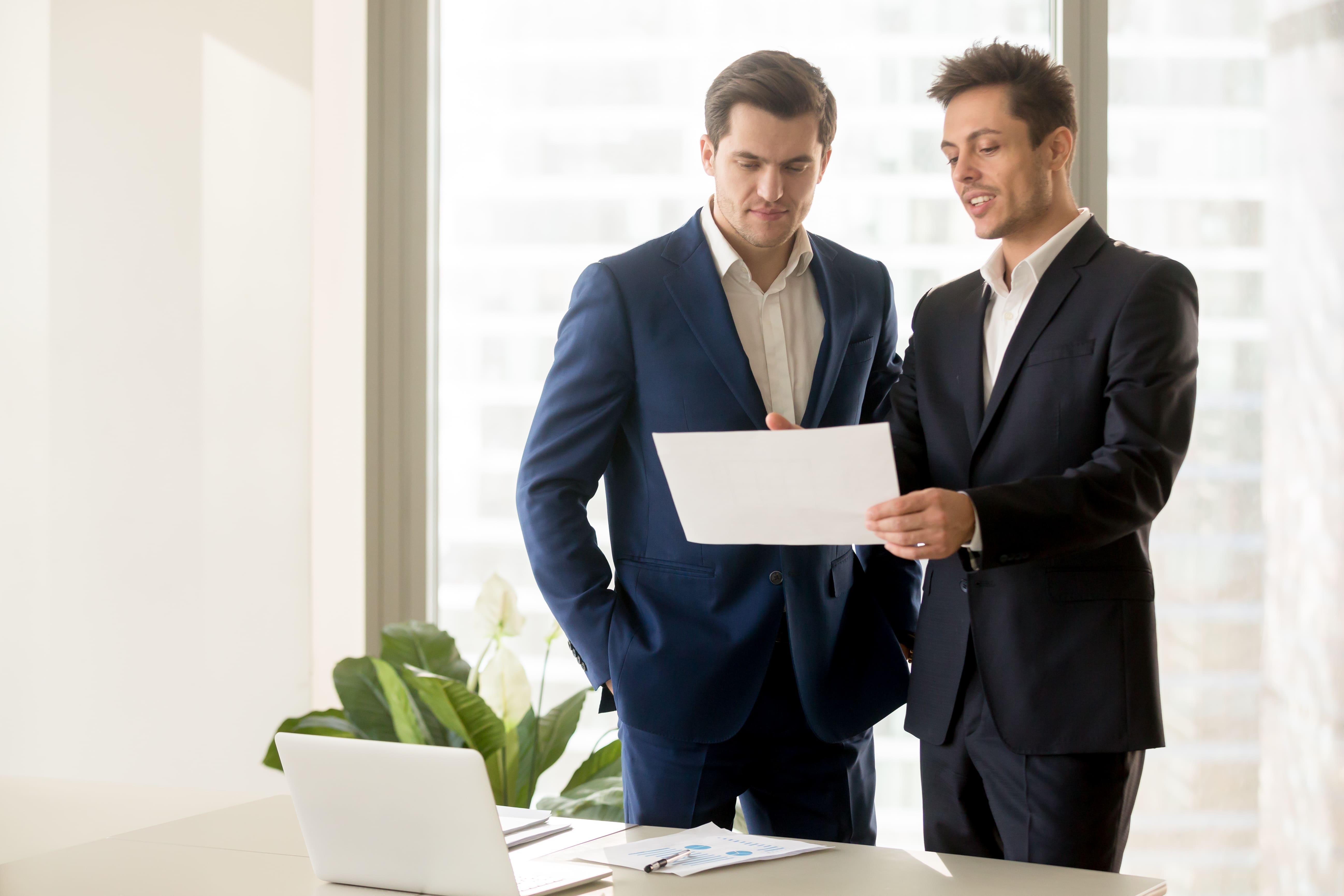 Imagem de duas pessoas lendo um papel depois que elas viram como elas podem melhorar o ambiente de trabalho