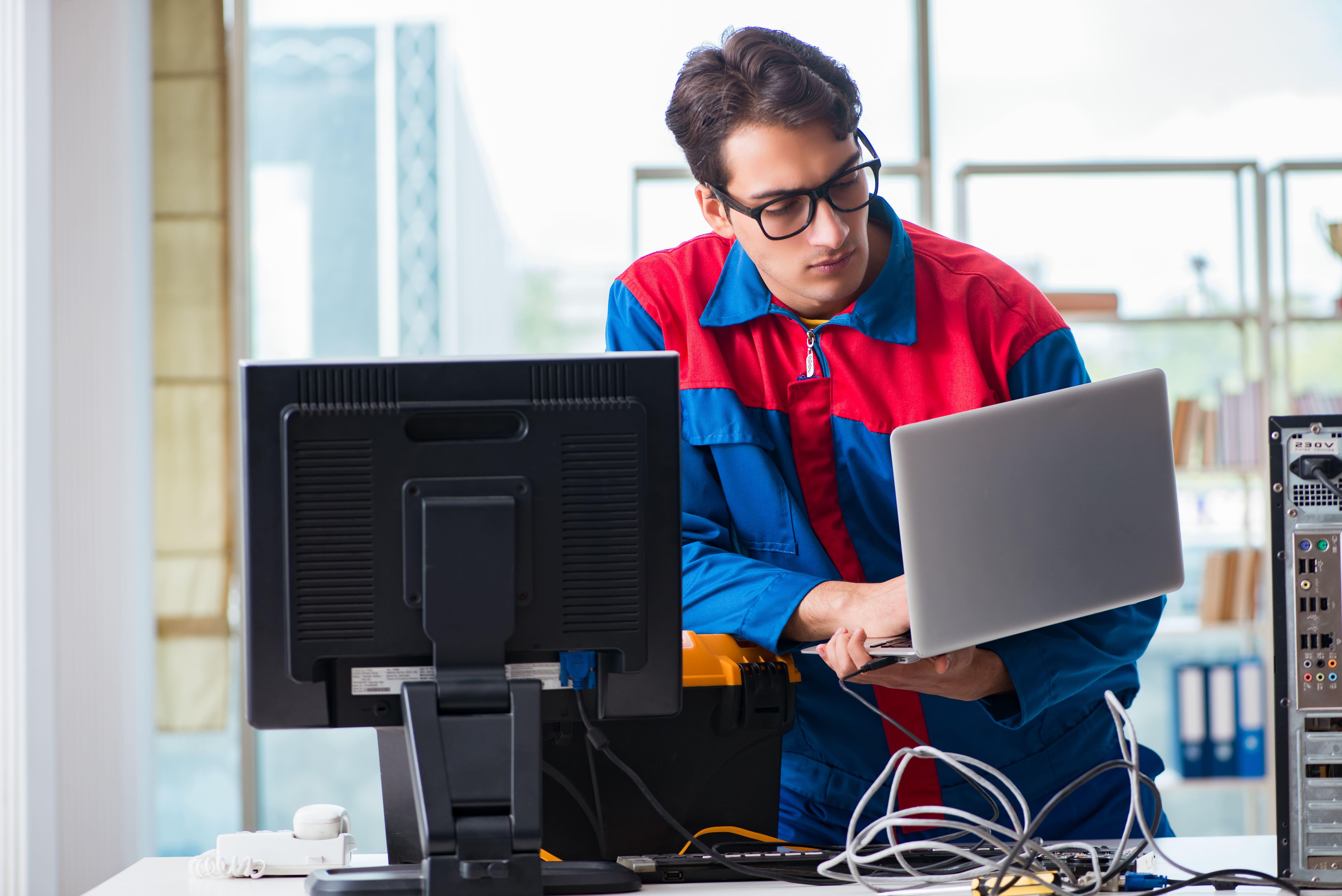 Imagem de um técnico em informática arrumando um computador de uma empresa para inspirar os profissionais que querem abrir uma assistência técnica em informática