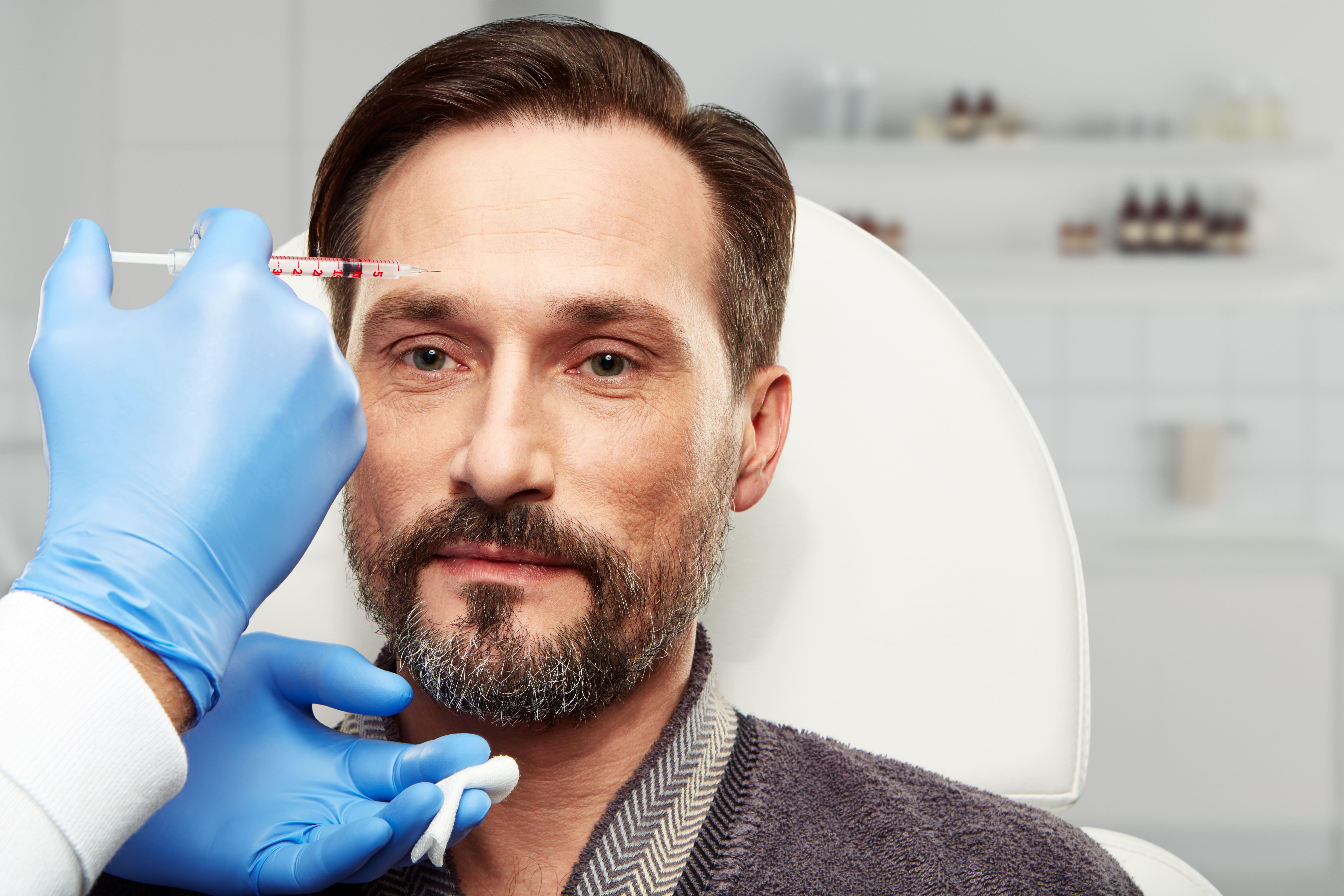 Foto de um homem aplicando botox depois de ver um anúncio de um empreendedor que resolveu abrir um centro estético próximo a sua residência