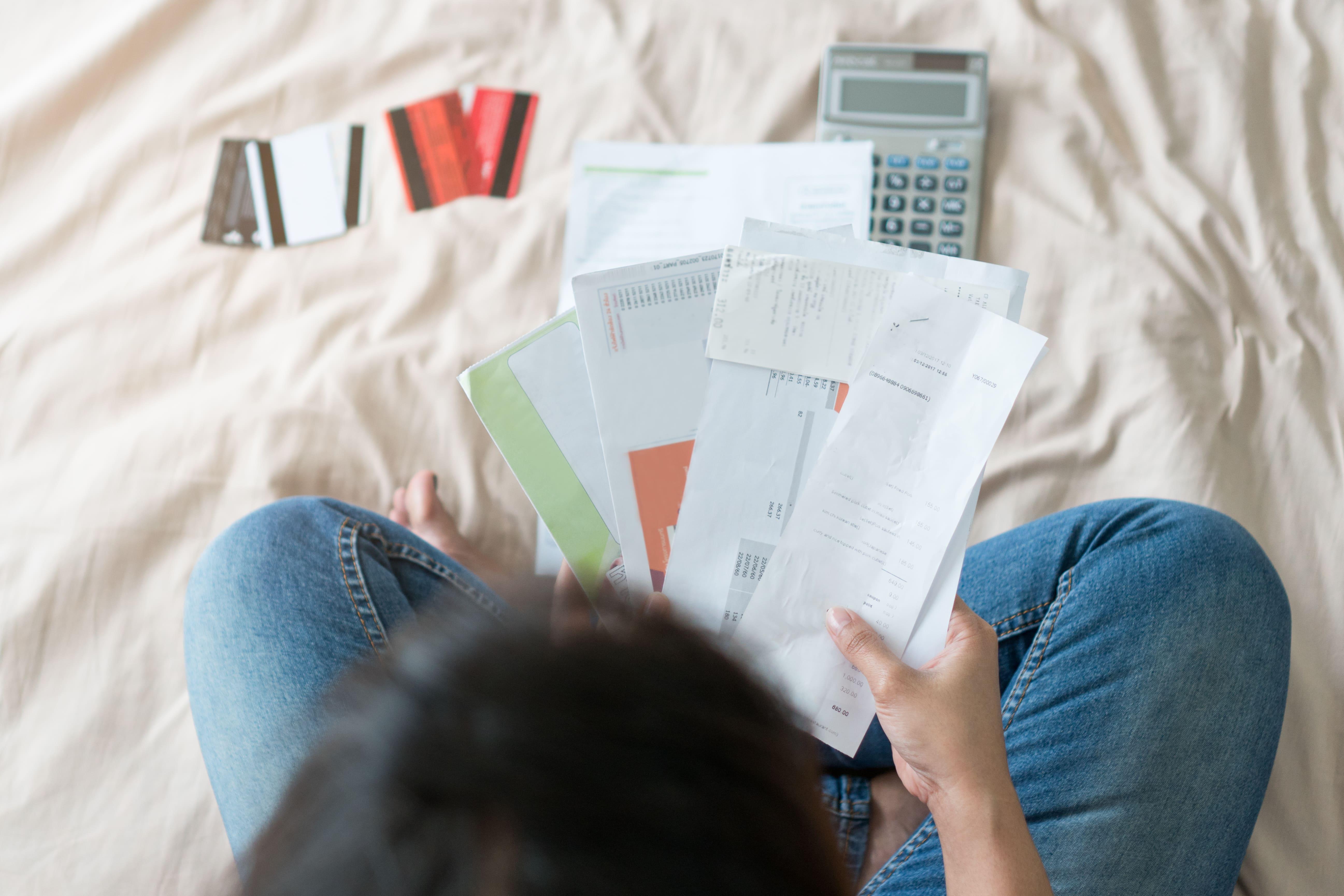 Imagem de uma mulher com todas as suas contas pendentes remetendo ao cancelamento ao programa PERT por falta de pagamento