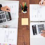 foto de pessoas fazendo cálculos de impostos, representando a contabilidade tributária