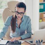 foto de uma mulher fazendo cálculos, representando a importância da contabilidade