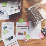 Foto de pessoas mexendo em notebooks e papeis, representando a Importância do Marketing Contábil
