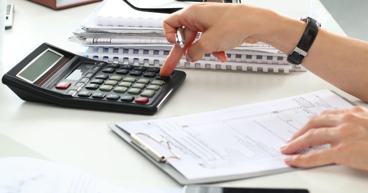 foto de uma pessoa mexendo em calculadora e fazendo os cálculos do IRPF 2019