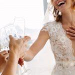 Imagem de uma noiva brindando a escolha do seu vestido depois que alguém decidiu abrir uma loja de confecção de vestidos de noiva