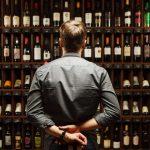 Imagem de um empreendedor olhando seus produtos depois que ele resolveu montar uma adega