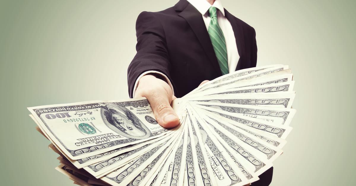 Imagem de um homem segurando dinheiro para aqueles empreendedores que querem ganhar mais dinheiro depois que fizerem a mudança de comportamento