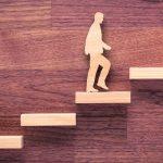 Imagem de alguns degraus e um homem subindo para remeter como a pessoa pode subir na vida quando ela busca recuperar a sua motivação
