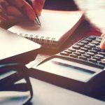 Imagem de um empreendedor fazendo os cálculo para ver se consegue pegar um microcrédito para a sua empresa
