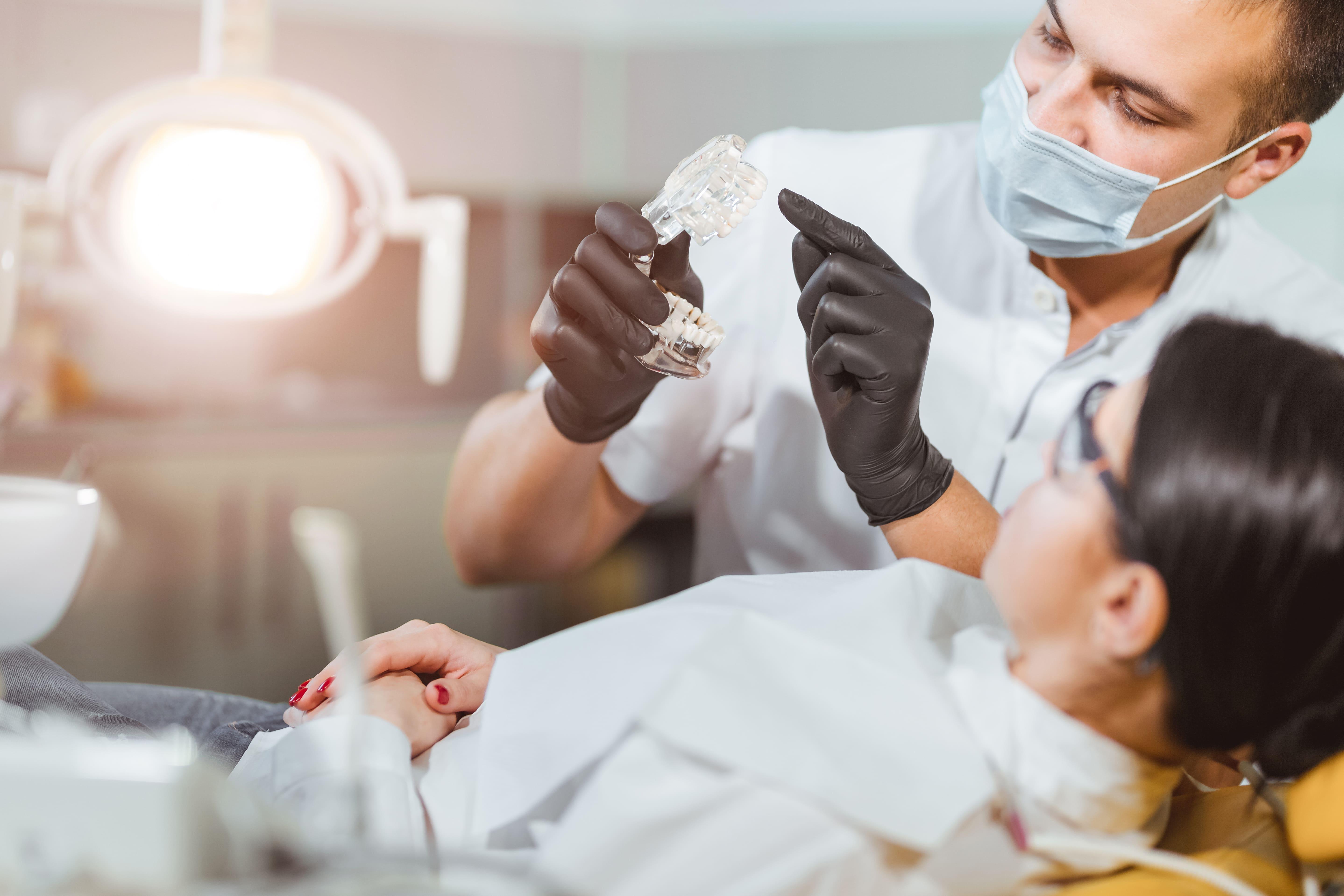 Imagem de um dentista atendendo uma paciente depois que ele decidiu abrir uma clínica odontológica