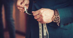 Imagem de um homem com uma fita métrica na mão para remeter o empreendedor que quer abrir uma alfaiataria
