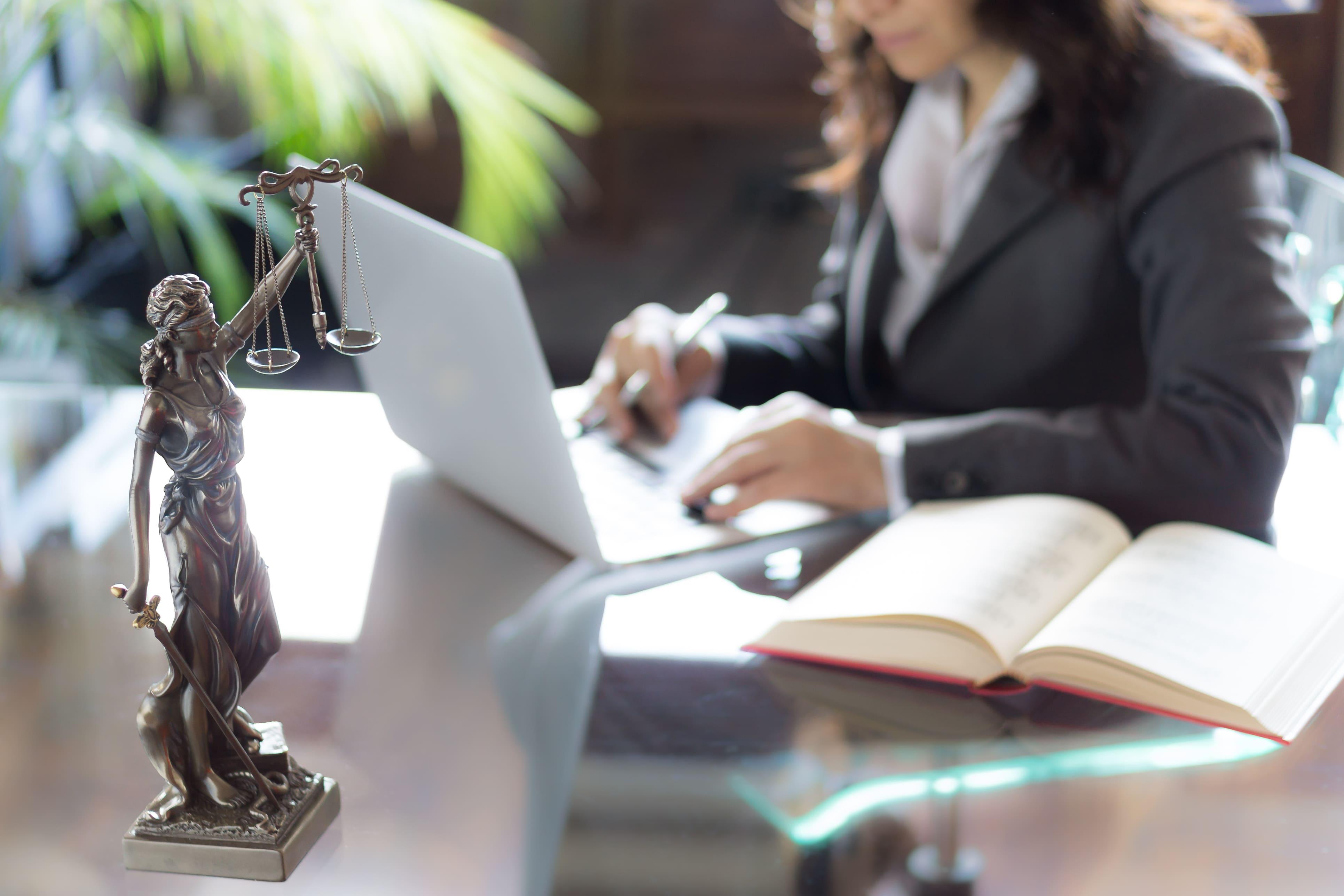Imagem de uma advogada sentada na sua mesa depois que ela resolveu abrir um escritório de advocacia