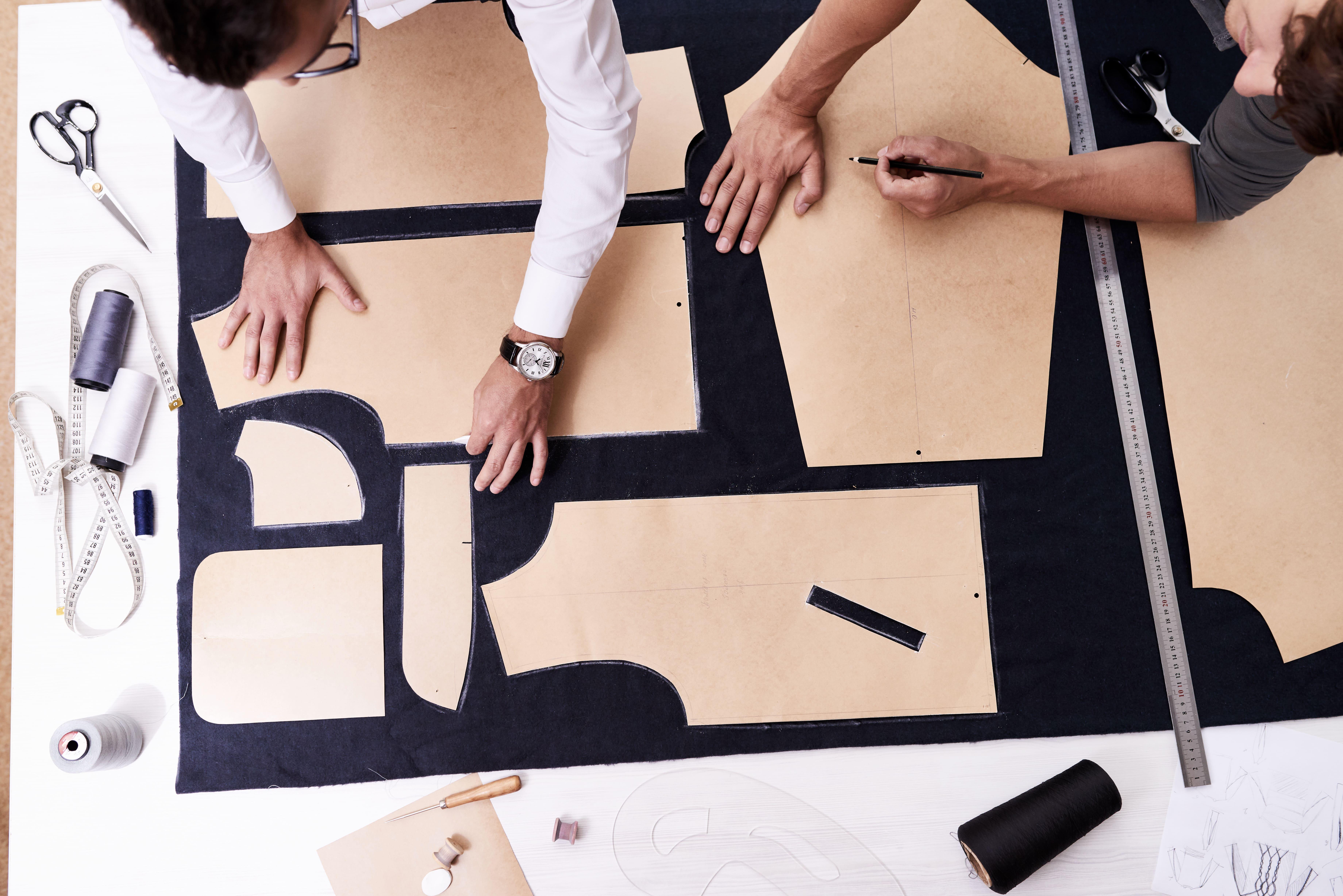 Imagem de uma mesa com vários cortes de roupa para quem deseja abrir uma alfaiataria