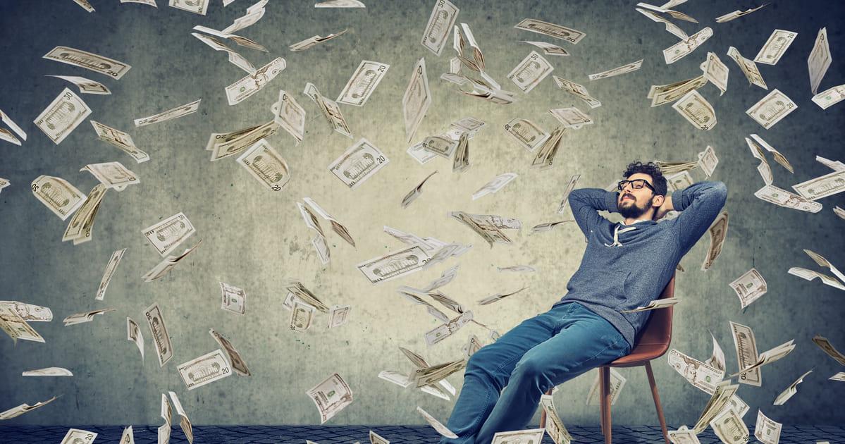 Imagem de um homem no meio do dinheiro para remeter a independência financeira