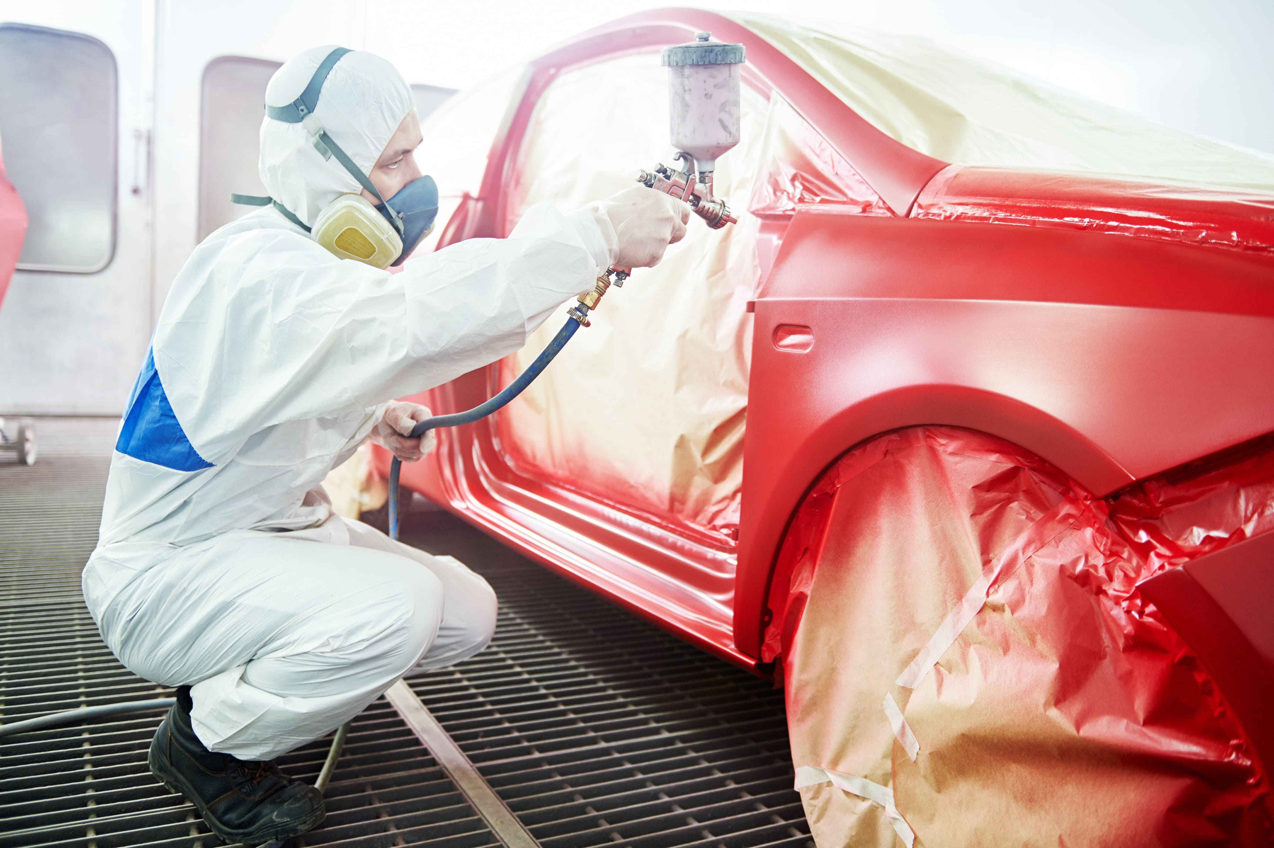 Imagem de um profissional pintando um carro para remeter ao empreendedor que deseja montar um serviço de funilaria e pintura