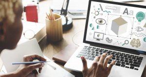 Mulher criando um site no computador para remeter ao empreendedor que deseja montar um serviço de criação de website