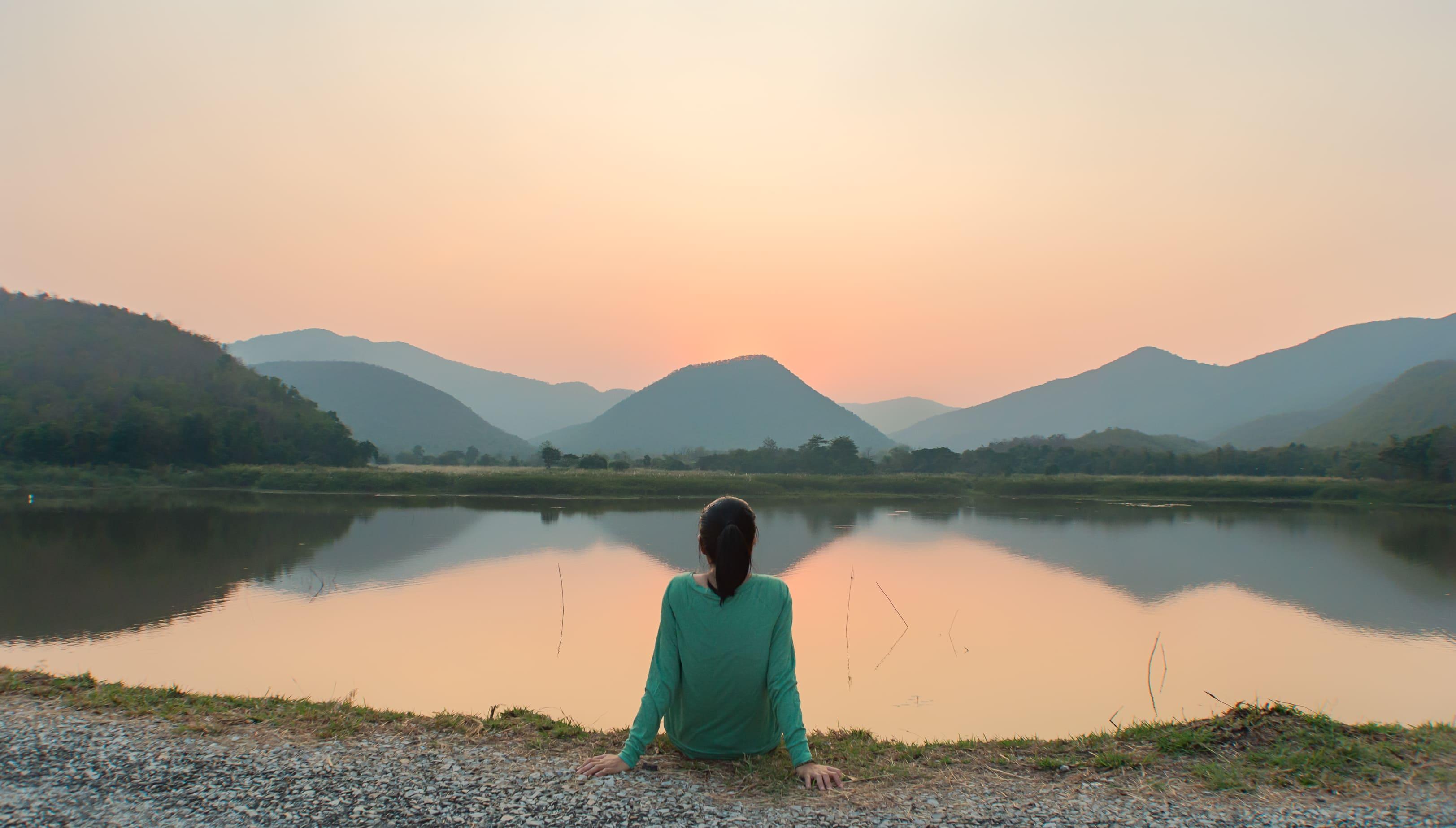 Imagem de uma mulher sentada na beira do lago praticando o mindfulness