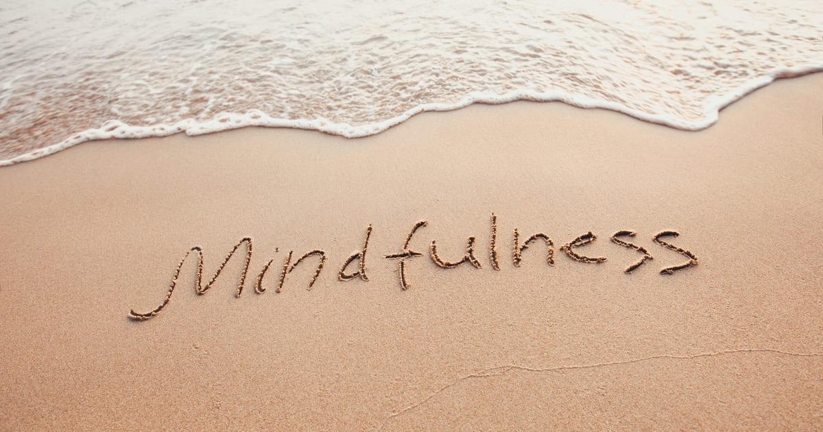 Imagem de uma praia que na areia está escrito a palavra mindfulness