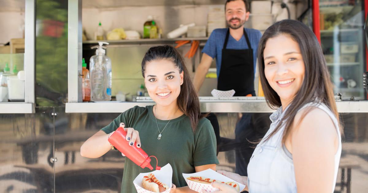 Imagem de duas pessoas comendo cachorro-quente para remeter ao empreendedor que deseja montar um carrinho de cachorro-quente
