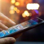 Imagem de um homem com um celular na mão comprando algo por um aplicativo para remeter ao m-commerce retratado no texto