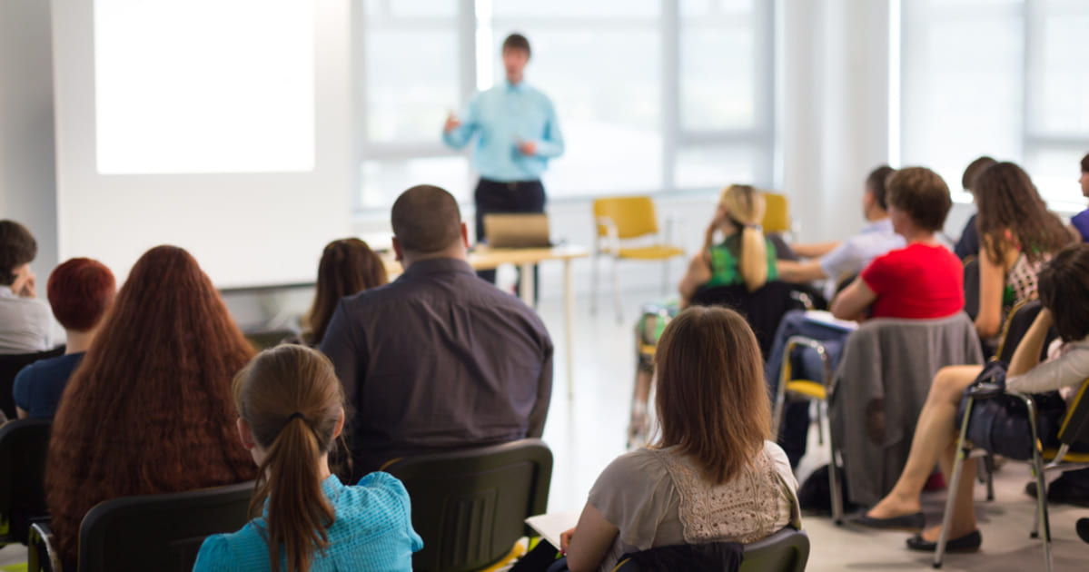 Sala de aula com alunos e um professor à frente explicando, representando a Contabilidade para Instituições de ensino
