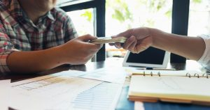 Imagem de um agente bancário repassando dinheiro para um empreendedor para remeter aos benefícios de uma conta jurídica para a sua empresa