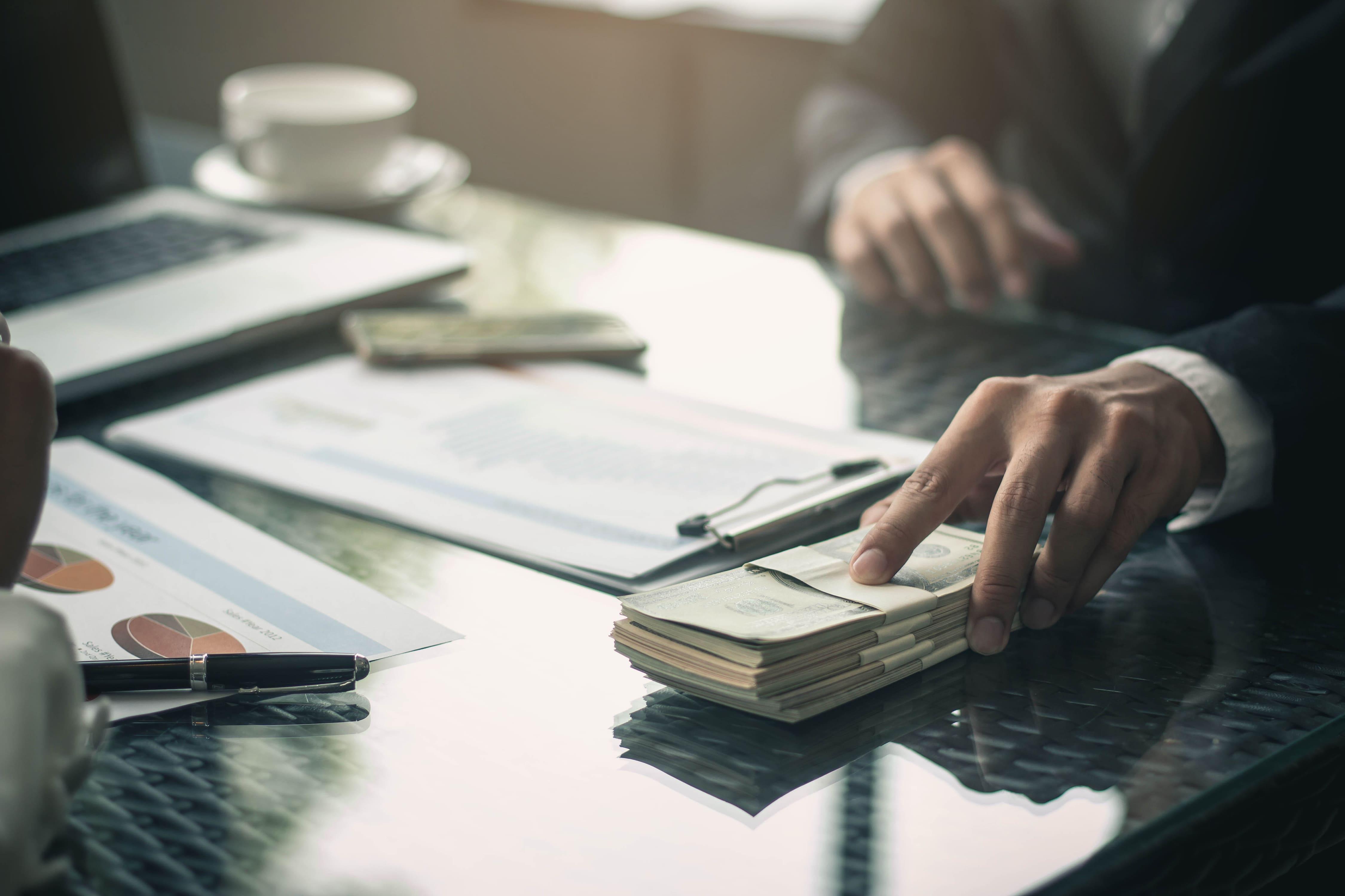 Imagem de um homem segurando um dinheiro em cima da mesa para remeter ao sucesso financeiro