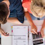 Imagem de um casal de empreendedores fazendo os cálculos de quanto vão investir para contratarem colaboradores temporários