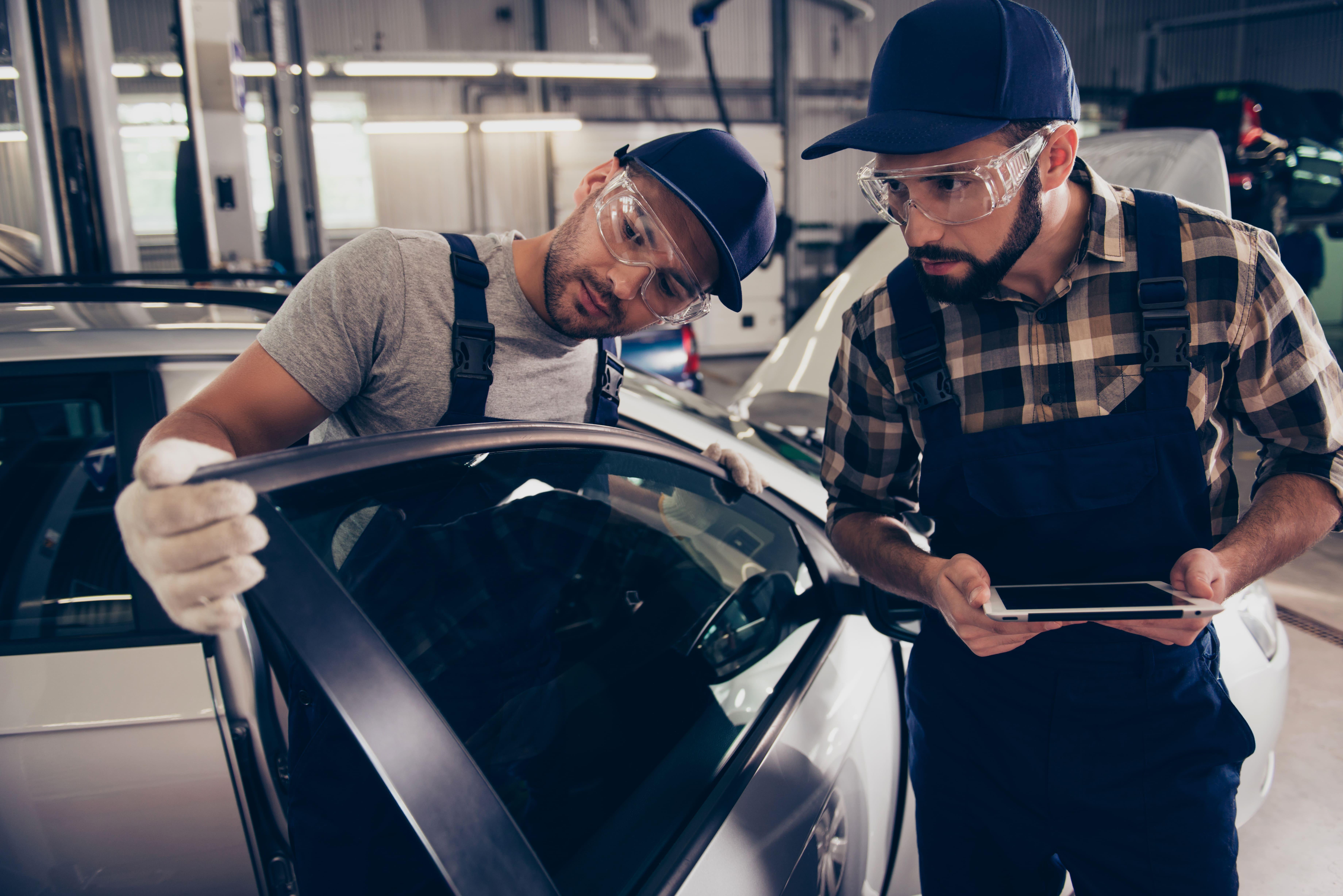 Imagem de dois homens medindo a intensidade do vidro do carro para remeter ao empreendedor que deseja montar um serviço de cromagem