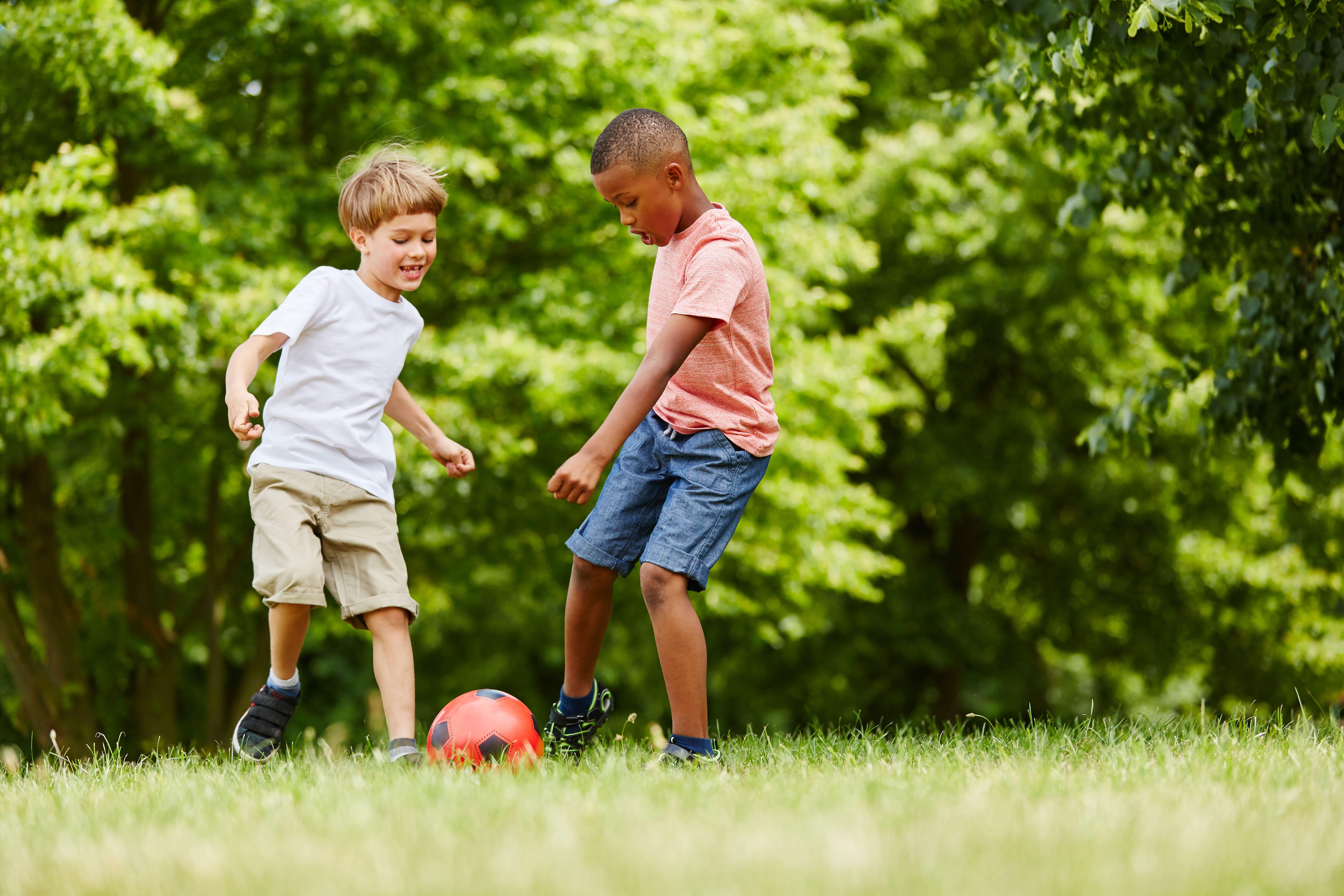 Imagem de dois meninos jogando bola para remeter ao texto que mostra como montar uma colônia de férias