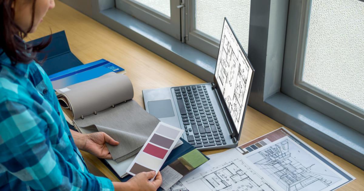 Arquiteta trabalhando na escolha de cores com um notebook representando a contabilidade para arquitetura