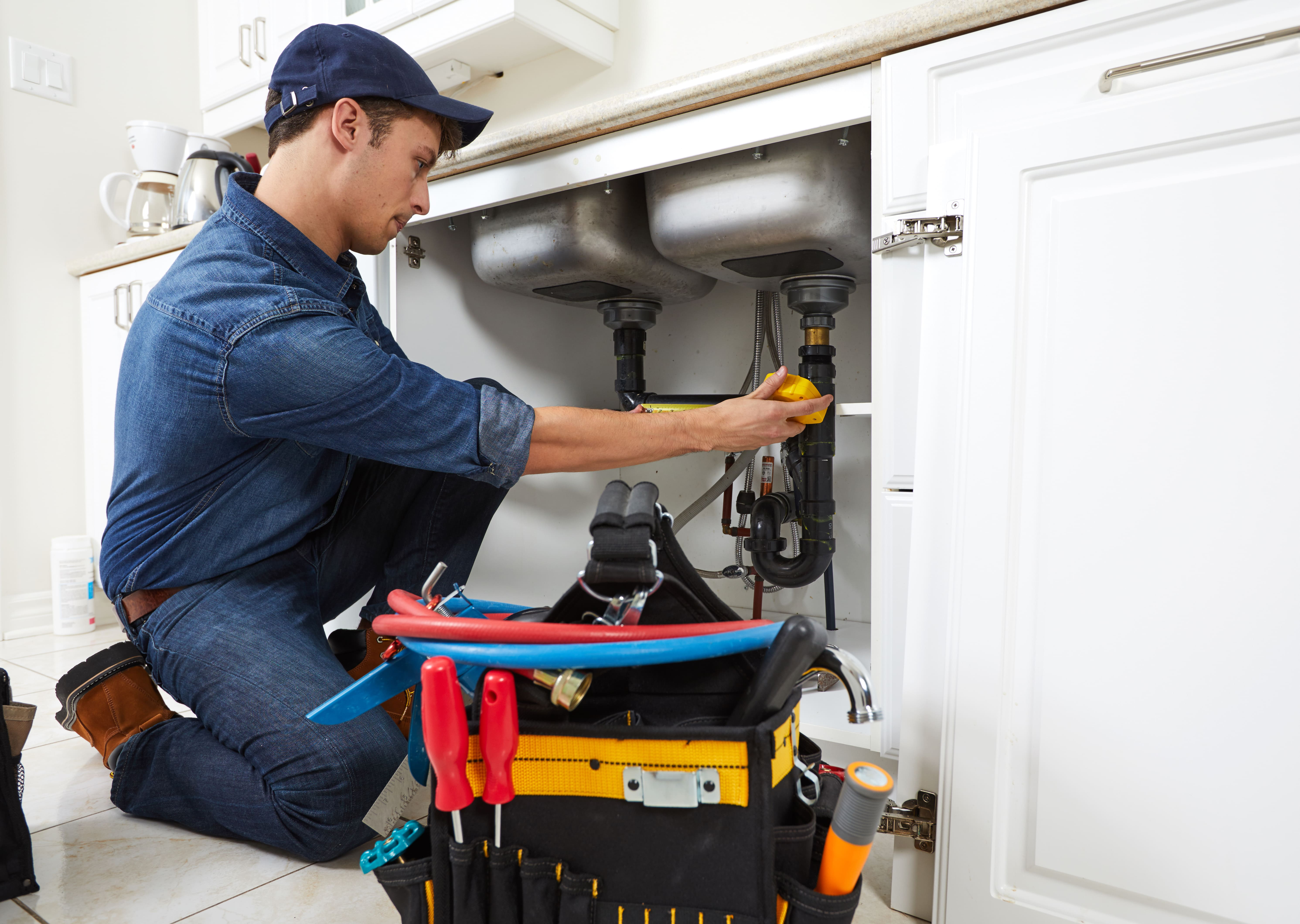 Imagem de um homem consertando a pia para inspirar o empreendedor sobre como montar um serviço de marido de aluguel
