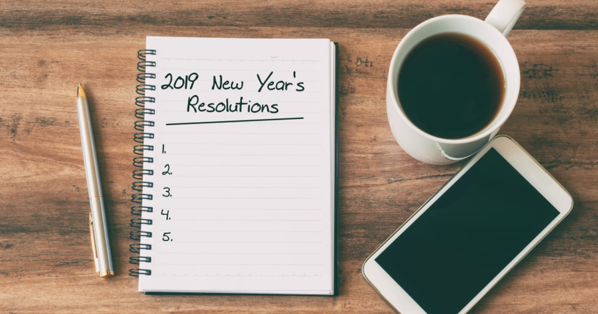 Foto de um caderno escrito resoluções de ano novo, uma xicara ao lado, um celular e uma caneta