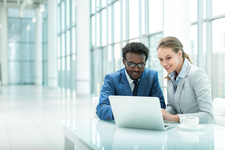 Imagem de duas pessoas procurando na internet como realizar o cadastro na Previdência Social