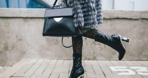 Imagem de uma mulher com usando dois produtos para inspirar quem deseja abrir uma loja de bolsas e calçados