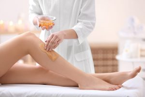 Foto de mulher fazendo depilação na perna de outra, representando como abrir uma clínica de depilação