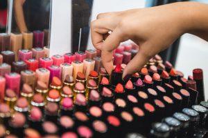 foto de uma mulher pegando batom, representando como abrir uma loja de maquiagem