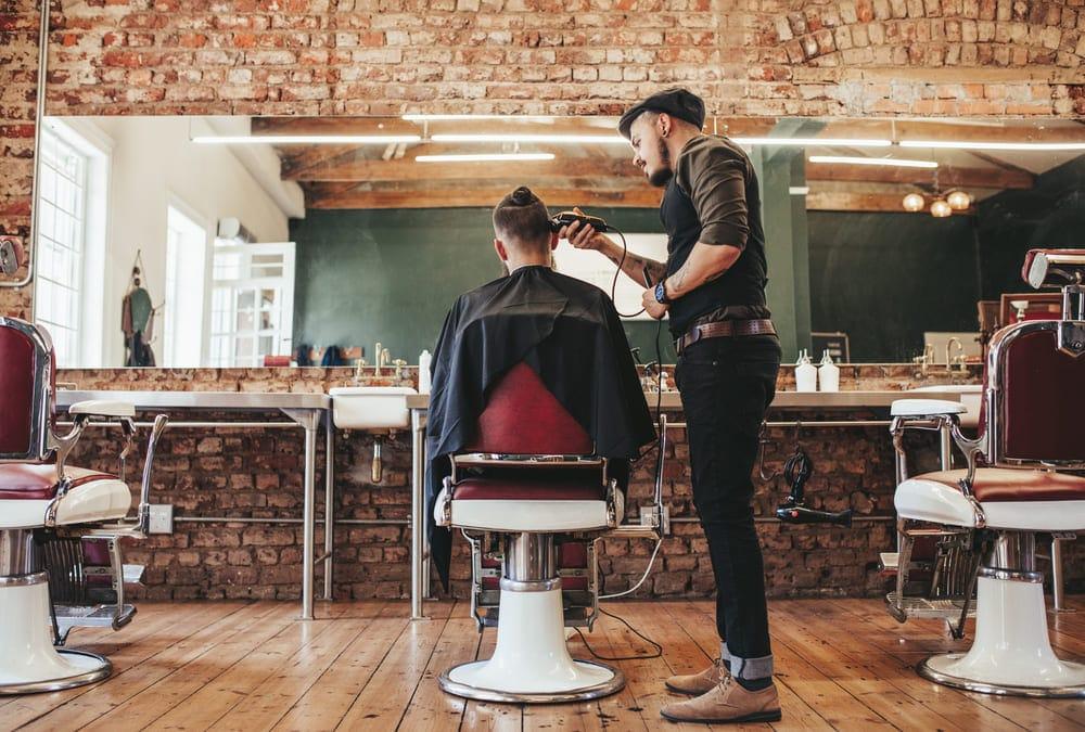 Foto de um barbeiro cortando cabelo de um freguês, representando como abrir mei barbeiro